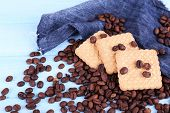 Shortbread cookies with spilled coffee beans on blue wooden background with jeans material