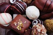 Many chocolate candy on wooden rustic background
