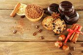 Chocolate cookies with bowl of cocoa, nuts, coffee beans, slice of lemon and cinnamon on rustic background