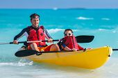Father and son kayaking at tropical ocean