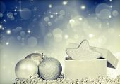 Sparkling Christmas background with silver Christmas balls and gift box