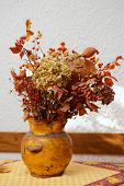 Dried bouquet in pot against the wall, still life