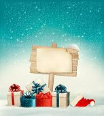 Winter christmas with a sign, gift boxes and a santa hat background.