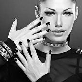 Beautiful woman with black nails and  with bracelet thorns on the neck