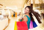 Beautiful attractive young brunette woman carrying shopping bags