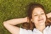 Overhead of pretty redhead smiling lying on grass