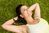 Relaxed fit brunette lying on grass in the park