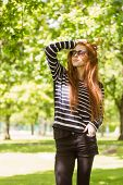 Beautiful young woman in sunglasses standing at the park