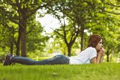 Pretty redhead thinking and lying on grass in park