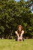 Portrait of a pretty redhead smiling stretching in park