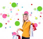 Stylish blonde smiling with shopping bags against dot pattern