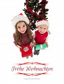 Festive little siblings smiling at camera holding gifts against border