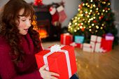 Surprised redhead holding present at christmas at home in the living room