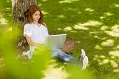 Pretty redhead typing on her laptop in park on a sunny day