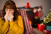 Woman sitting on sofa and blowing her nose at christmas at home in the living room