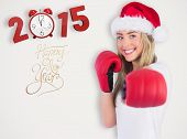 Festive blonde punching with boxing gloves against grey background with vignette