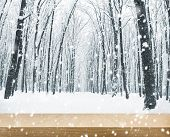 Panorama of winter forest with trees covered snow and wooden table