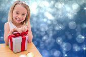 Festive little girl opening a gift against shimmering light design on blue