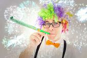 Geeky hipster wearing a rainbow wig blowing party horn against colourful fireworks exploding on black background