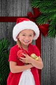 Cute little girl wearing santa hat holding baubles against wood with festive bow