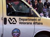 NEW YORK - NOV 11, 2014: A man driving a Department of Veterans Affairs van waves an American Flag during the 2014 America's Parade held on Veterans Day in New York City on November 11, 2014.