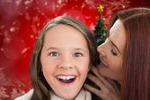 Mother and daughter telling secrets against christmas tree