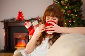 Pretty redhead sitting on couch drinking hot chocolate at christmas at christmas at home in the living room