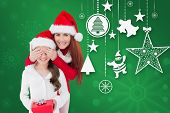 Mother and daughter with gift against green snowflake background