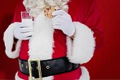 Santa holding cookie and glass of milk against red snowflake background