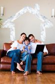 Family using a laptop with thumbs up and copyspace against house outline in clouds