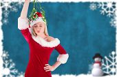 Festive cute blonde holding mistletoe against blurred christmas frame