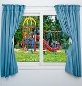 stock photo of swing  - swing carousel in the park for children view out the window - JPG
