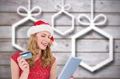 Festive blonde woman using her credit card and tablet pc against blurred christmas background