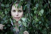 Woman Peering Through Leaves