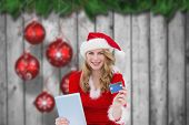 Woman holding a tablet against christmas baubles hanging over wood