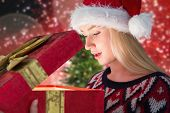 Festive blonde opening a gift against blurred christmas tree background
