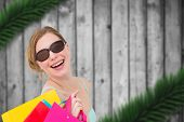 Portrait of a woman holding shopping bags wearing sunglasses against blurred fir branches on wood
