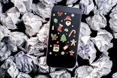 Christmas graphics against smartphone on crumpled paper