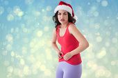 Festive fit brunette pinching her stomach against blue abstract light spot design