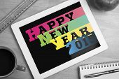 Colourful happy new year against overhead of tablet on desk