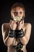 stock photo of sadomasochism  - beautiful woman slave in handcuffs with flower in hand - JPG