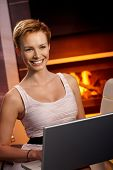 Beautiful young woman using laptop computer at home by fireplace, smiling happy.