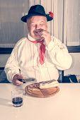 Man Wearing Traditional Clothing Enjoying Bacon