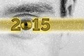 picture of superimpose  - Creative 2015 New Year background with the date in a golden banner superimposed over a greyscale face of a man with the eye forming the 0 in the date and falling snow flakes with copyspace - JPG