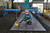 Worker Fixes Magnetic Lifters Lift Plane Of Steel Sheet.