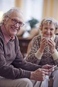 Happy grandfather in eyeglasses looking at camera with his wife on background