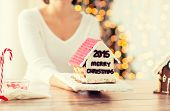 cooking, people, christmas and baking concept - close up of happy woman holding and showing gingerbread house at home