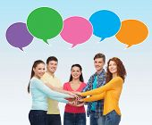 friendship, communication, gesture and people concept - group of smiling teenagers with hands on top of each other over blue background with text bubbles