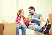 moving, home and couple concept - smiling couple with coffee or tea cups relaxing on sofa in new home