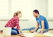 repair, building and home concept - smiling couple measuring wallpaper